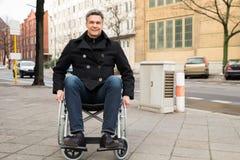 Με ειδικές ανάγκες άτομο στην αναπηρική καρέκλα στην πόλη στοκ εικόνα