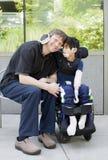Με ειδικές ανάγκες αγόρι που αγκαλιάζει τον πατέρα περιμένοντας στο νοσοκομείο Στοκ εικόνες με δικαίωμα ελεύθερης χρήσης