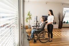 Με ειδικές ανάγκες ανώτερη γυναίκα στην αναπηρική καρέκλα με το νέο daugher της Στοκ Εικόνα