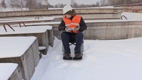Με ειδικές ανάγκες εργάτης στην αναπηρική καρέκλα που χρησιμοποιεί το PC ταμπλετών απόθεμα βίντεο
