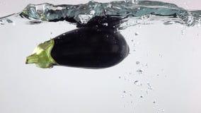 Μελιτζάνα που εμπίπτει κάτω στο νερό με τους παφλασμούς, έξοχο σε αργή κίνηση βίντεο φιλμ μικρού μήκους