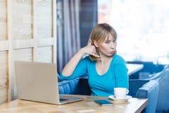 Με καλέστε! Το πορτρέτο του όμορφου νέου κοριτσιού με ξανθό ακούει στην μπλε μπλούζα κάθεται στον καφέ και φλερτάρει με σας, παρο στοκ εικόνες