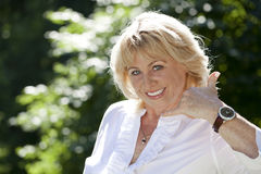 Με καλέστε, πορτρέτο της καλής μέσης ηλικίας γυναίκας στο θερινό πάρκο Στοκ Φωτογραφία