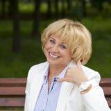 Με καλέστε, πορτρέτο της καλής μέσης ηλικίας γυναίκας στο θερινό πάρκο Στοκ φωτογραφία με δικαίωμα ελεύθερης χρήσης