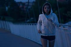 Με κουκούλα γυναίκα που τρέχει στο πάρκο τη νύχτα Στοκ Εικόνες