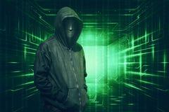Με κουκούλα με την ανώνυμη μάσκα που στέκεται με το δυαδικό κώδικα στοκ φωτογραφίες