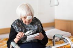 Με οπτική αναπηρία ηλικιωμένη χρονών συνεδρίαση γυναικών 95 στην κακή προσπάθεια να διαβάσει με την ενίσχυση - γυαλί Στοκ φωτογραφία με δικαίωμα ελεύθερης χρήσης