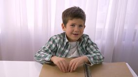 Με οπτική αναπηρία μικρό βιβλίο μπράιγ ανάγνωσης αγοριών με την πηγή συμβόλων για την τυφλή συνεδρίαση στον πίνακα απόθεμα βίντεο