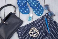 με την μπλε τσάντα, τα γυαλιά ηλίου, τις πτώσεις κτυπήματος, τη στιλβωτική ουσία καρφιών και λίγο αεροπλάνο στο άσπρο ξύλινο υπόβ Στοκ Φωτογραφία