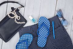 με την μπλε τσάντα, τα γυαλιά ηλίου, τις πτώσεις κτυπήματος, τη στιλβωτική ουσία καρφιών και λίγο αεροπλάνο στο άσπρο ξύλινο υπόβ Στοκ εικόνα με δικαίωμα ελεύθερης χρήσης