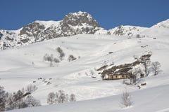 Με τις χιονώδεις καλύβες βουνών στις Άλπεις Στοκ Εικόνες