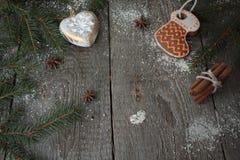 Μελόψωμο, διακόσμηση Χριστουγέννων, δέντρο έλατου, χιόνι στο ξύλινο υπόβαθρο, κανέλα Στοκ Φωτογραφία