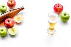 Μηλίτης της Apple που χύνεται στο γυαλί κοντά στο μπουκάλι και τα μήλα Άσπρο διάστημα αντιγράφων άποψης υποβάθρου τοπ Στοκ Φωτογραφία