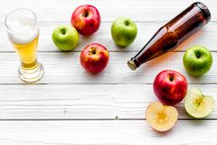 Μηλίτης της Apple που χύνεται στο γυαλί κοντά στο μπουκάλι και τα μήλα Άσπρο ξύλινο διάστημα αντιγράφων άποψης υποβάθρου τοπ Στοκ Φωτογραφίες