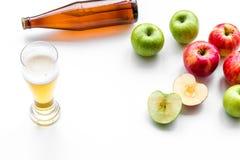 Μηλίτης της Apple που χύνεται στο γυαλί κοντά στο μπουκάλι και τα μήλα Άσπρο διάστημα αντιγράφων άποψης υποβάθρου τοπ Στοκ Εικόνες