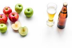 Μηλίτης της Apple που χύνεται στο γυαλί κοντά στο μπουκάλι και τα μήλα Άσπρο διάστημα αντιγράφων άποψης υποβάθρου τοπ Στοκ φωτογραφία με δικαίωμα ελεύθερης χρήσης
