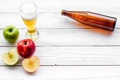 Μηλίτης της Apple που χύνεται στο γυαλί κοντά στο μπουκάλι και τα μήλα Άσπρο ξύλινο διάστημα αντιγράφων άποψης υποβάθρου τοπ Στοκ Εικόνες