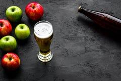 Μηλίτης της Apple που χύνεται στο γυαλί κοντά στο μπουκάλι και τα μήλα Μαύρο διάστημα αντιγράφων άποψης υποβάθρου τοπ Στοκ εικόνες με δικαίωμα ελεύθερης χρήσης