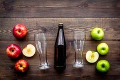 Μηλίτης της Apple Χαμηλός-οινοπνευματώδης beveradge στο σκοτεινό μπουκάλι κοντά στα γυαλιά μπύρας και τα φρέσκα μήλα στη σκοτεινή Στοκ εικόνες με δικαίωμα ελεύθερης χρήσης