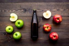 Μηλίτης της Apple Χαμηλός-οινοπνευματώδης beveradge στο σκοτεινό μπουκάλι στη σκοτεινή ξύλινη τοπ άποψη υποβάθρου Στοκ Φωτογραφία