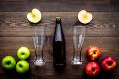 Μηλίτης της Apple Χαμηλός-οινοπνευματώδης beveradge στο σκοτεινό μπουκάλι κοντά στα γυαλιά μπύρας και τα φρέσκα μήλα στη σκοτεινή Στοκ Εικόνες