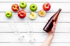Μηλίτης της Apple Χαμηλός-οινοπνευματώδης beveradge στο σκοτεινό μπουκάλι κοντά στα γυαλιά μπύρας και τα φρέσκα μήλα στην άσπρη ξ Στοκ Φωτογραφίες