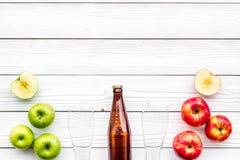 Μηλίτης της Apple Χαμηλός-οινοπνευματώδης beveradge στο σκοτεινό μπουκάλι κοντά στα γυαλιά μπύρας και τα φρέσκα μήλα στην άσπρη ξ Στοκ Εικόνες