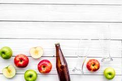 Μηλίτης της Apple Χαμηλός-οινοπνευματώδης beveradge στο σκοτεινό μπουκάλι κοντά στα γυαλιά μπύρας και τα φρέσκα μήλα στην άσπρη ξ Στοκ φωτογραφίες με δικαίωμα ελεύθερης χρήσης