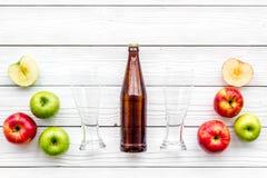 Μηλίτης της Apple Χαμηλός-οινοπνευματώδης beveradge στο σκοτεινό μπουκάλι κοντά στα γυαλιά μπύρας και τα φρέσκα μήλα στην άσπρη ξ Στοκ φωτογραφία με δικαίωμα ελεύθερης χρήσης