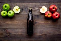 Μηλίτης της Apple Χαμηλός-οινοπνευματώδης beveradge στο σκοτεινό μπουκάλι στο σκοτεινό ξύλινο διάστημα αντιγράφων άποψης υποβάθρο Στοκ Εικόνα