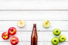 Μηλίτης της Apple Χαμηλός-οινοπνευματώδης beveradge στο σκοτεινό μπουκάλι κοντά στα γυαλιά μπύρας και τα φρέσκα μήλα στην άσπρη ξ Στοκ Εικόνα
