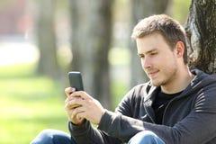 Μηνύματα ανάγνωσης αγοριών σε ένα έξυπνο τηλέφωνο υπαίθρια Στοκ Φωτογραφία