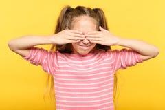 Μην δείτε κανένα κακό χαμογελώντας κορίτσι τα χέρια ματιών στοκ εικόνα