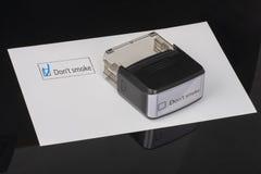 Μην καπνίστε - τετραγωνίδιο με έναν κρότωνα στη Λευκή Βίβλο με λαστιχένιο Stamper λαβών Έννοια πινάκων ελέγχου στοκ φωτογραφίες με δικαίωμα ελεύθερης χρήσης