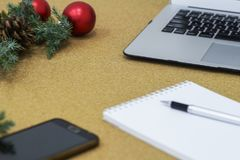Μην ολοκληρωμένος κατάλογος στόχων σε ένα σημειωματάριο σε έναν ξύλινο πίνακα με τις διακοσμήσεις Χριστουγέννων και ένα lap-top Στοκ Φωτογραφίες