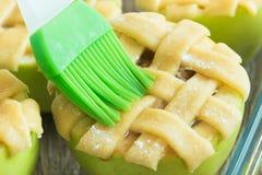 Μην ψημένα μήλα με τη βούρτσα και το αυγό στοκ εικόνες