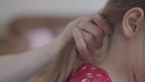 Μητέρα ή πατέρας που κτενίζει ήπια την ξανθή τρίχα της χαριτωμένης κόρης με την επαγγελματική χτένα o απόθεμα βίντεο