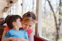 Μητέρα αγκαλιάσματος αγοριών στο τραίνο Στοκ εικόνες με δικαίωμα ελεύθερης χρήσης