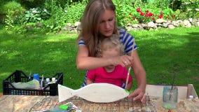 Μητέρα ζωγράφων με την ξύλινη διακόσμηση ψαριών χρωμάτων κοριτσιών κορών μικρών παιδιών της απόθεμα βίντεο