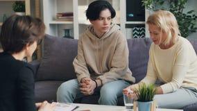 Μητέρα και έφηβος γιος που μιλούν στον ψυχολόγο στο γραφείο που αγκαλιάζει και που χαμογελά απόθεμα βίντεο