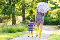 Μητέρα και λίγη λατρευτή κόρη στις κίτρινες λαστιχένιες μπότες Στοκ Φωτογραφίες
