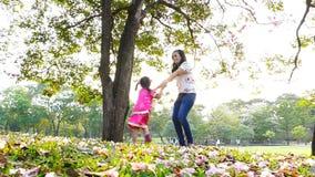 Μητέρα και λίγη κόρη που παίζουν μαζί σε ένα πάρκο φιλμ μικρού μήκους