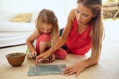 Μητέρα και λίγη κόρη που σύρουν μαζί τις εικόνες Στοκ Εικόνες