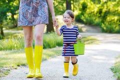 Μητέρα και λίγο λατρευτό παιδί στις κίτρινες λαστιχένιες μπότες Στοκ εικόνες με δικαίωμα ελεύθερης χρήσης