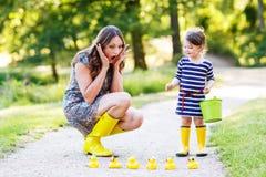 Μητέρα και λίγο λατρευτό παιδί στις κίτρινες λαστιχένιες μπότες Στοκ Φωτογραφίες