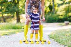 Μητέρα και λίγο λατρευτό παιδί στις κίτρινες λαστιχένιες μπότες Στοκ φωτογραφία με δικαίωμα ελεύθερης χρήσης