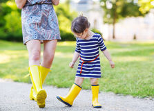 Μητέρα και λίγο λατρευτό παιδί στις κίτρινες λαστιχένιες μπότες Στοκ Εικόνα