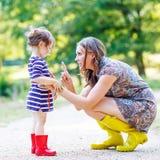 Μητέρα και λίγο λατρευτό παιδί στις κίτρινες λαστιχένιες μπότες Στοκ Εικόνες