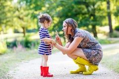 Μητέρα και λίγο λατρευτό παιδί στις κίτρινες λαστιχένιες μπότες Στοκ εικόνα με δικαίωμα ελεύθερης χρήσης