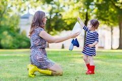 Μητέρα και λίγο λατρευτό παιδί στις κίτρινες και κόκκινες λαστιχένιες μπότες Στοκ φωτογραφία με δικαίωμα ελεύθερης χρήσης